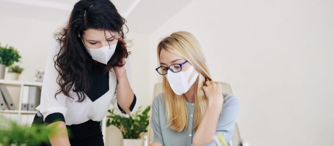 Businesswomen working in office and wearing surgical masks to prevent outbreak of corona virus or influenza