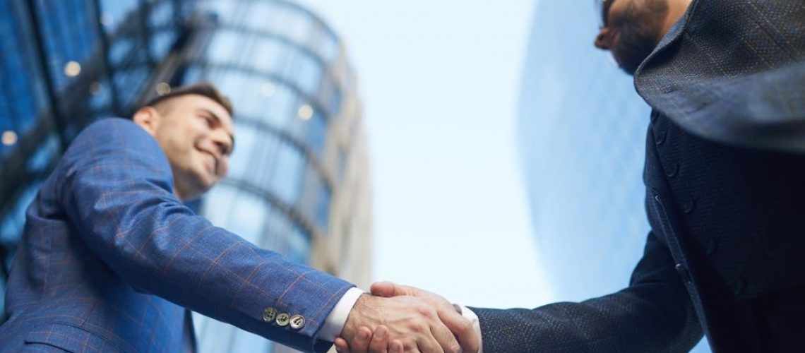 Low angle view of two young businessmen shaking hands during their meeting in the city