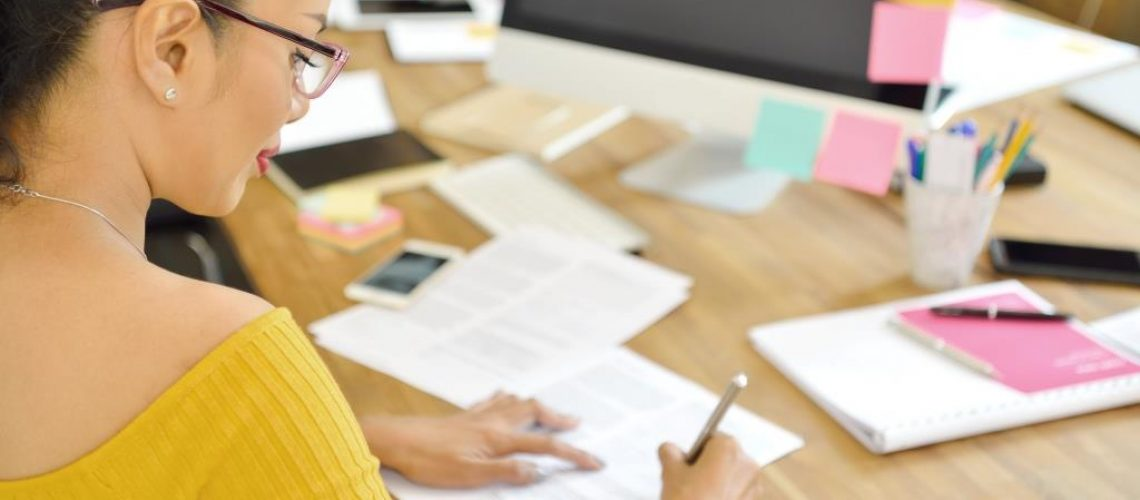 Businesswoman writing on document sitting in the office