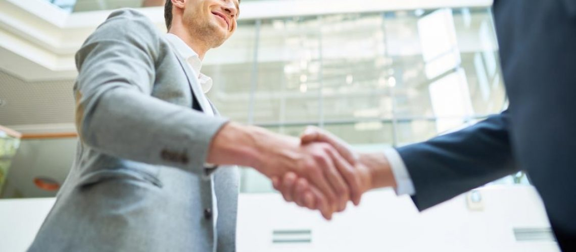 Low angle view of smiling business partners shaking hands while standing at spacious modern office lobby