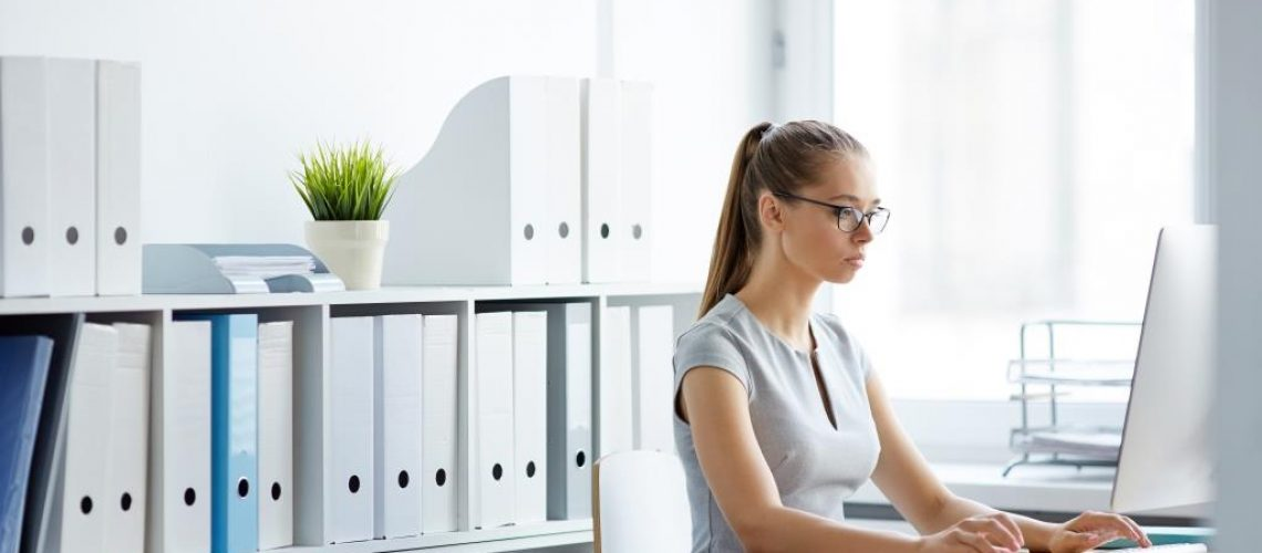 Serious businesswoman sitting in front of laptop in office