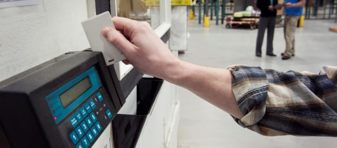 Person clocking in at a factory, time clock card
