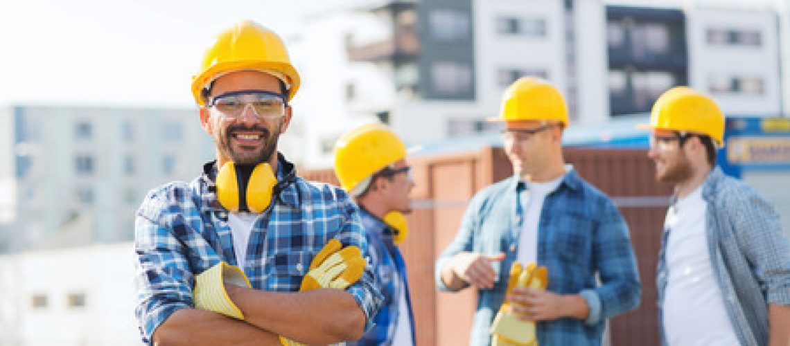 33301060 - business, building, teamwork and people concept - group of smiling builders in hardhats outdoors